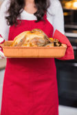 Mid section of woman holding roast turkey  — Stock Photo