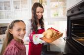 Smiling mother and daughter with roast turkey — Stock Photo