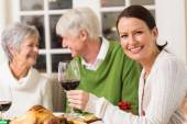 Portrait of woman toasting at camera during christmas dinner — Stockfoto