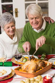 Man carving chicken while his wife having arm around him — Stock Photo