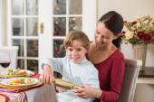 Little boy pulling a christmas cracker with his mother  — Stock Photo