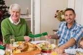 Smiling grandfather and father pulling christmas crackers  — Stock Photo