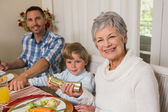 Smiling family pulling christmas crackers at the dinner table — Stock Photo