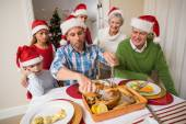 Father in santa hat carving chicken during dinner — Stock Photo