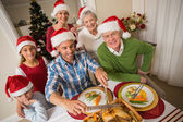 Father in santa hat carving chicken during christmas dinner — Stock Photo