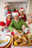 Grandfather in santa hat carving chicken during dinner — Stock Photo