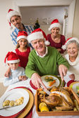 Grandfather in santa hat carving chicken at christmas dinner — Stock Photo