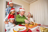 Grandfather in santa hat carving chicken at christmas  — Stock Photo