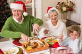 Grandfather in santa hat carving roast turkey at christmas — Stock Photo