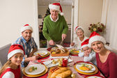 Grandfather in santa hat carving roast turkey at christmas dinne — Stock Photo