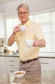 Senior man offering cup to camera — Stock Photo