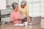Senior couple paying their bills with laptop — Stock Photo
