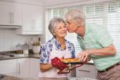 Senior man giving his wife a kiss while taking muffin — Stockfoto