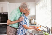 Senior couple washing vegetables at sink — Stock Photo