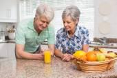 Senior couple looking at glass of orange juice — Stock Photo