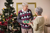 Senior couple swapping gifts by their christmas tree — Stock Photo