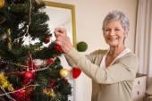 Äldre kvinna dekorera julgranen — Stockfoto