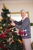 Senior man decorating the christmas tree — Stockfoto