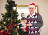 Senior man decorating the christmas tree — Stock Photo
