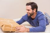 Happy man looking at package — Stock Photo