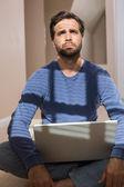 Depressed man sitting on floor using laptop — Stock Photo