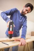 Casual man drilling hole in plank — Stock Photo