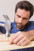 Casual man hammering nail in plank — Stock Photo