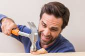 Casual man hammering his finger by accident — Stock Photo