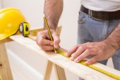 Casual man measuring plank of wood — Stock Photo