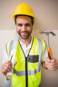 Construction worker holding spirit level and hammer — Stock Photo