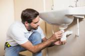 Plumber fixing the sink in a bathroom — Stock Photo