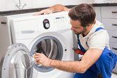 Handyman fixing a washing machine — Stock Photo