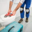 Plumber putting his tools on toilet — Stock Photo #60919107
