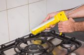Plumber putting filling in between tiles — Stockfoto