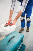 Plumber putting his tools on toilet — Stockfoto