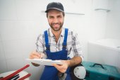 Plumber taking notes on clipboard — Stock Photo