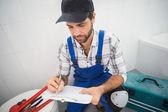 Plumber taking notes on clipboard — ストック写真