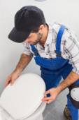 Plumber installing lid on toilet — Foto Stock