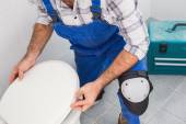 Plumber installing lid on toilet — Stock Photo