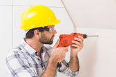 Construction worker drilling hole in wall — Stock Photo