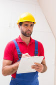 Construction worker taking notes on clipboard — Stock Photo