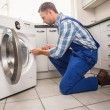 Handyman fixing a washing machine — Stock Photo #60927609