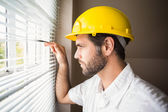 Handyman looking out the window — Stock Photo