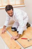 Carpenter putting down new wooden planks — Stock Photo