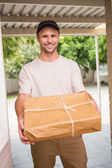 Delivery man offering parcel — Stock Photo