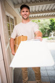 Delivery man showing clipboard to sign to customer — Stock Photo