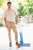 Happy delivery man leaning on trolley — Stock Photo