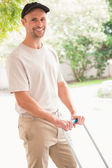 Happy delivery man pushing trolley — Stock Photo