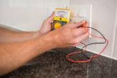 Metering voltage with digital multimeter — Stock Photo