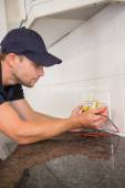 Electrician metering voltage with digital multimeter — Stockfoto